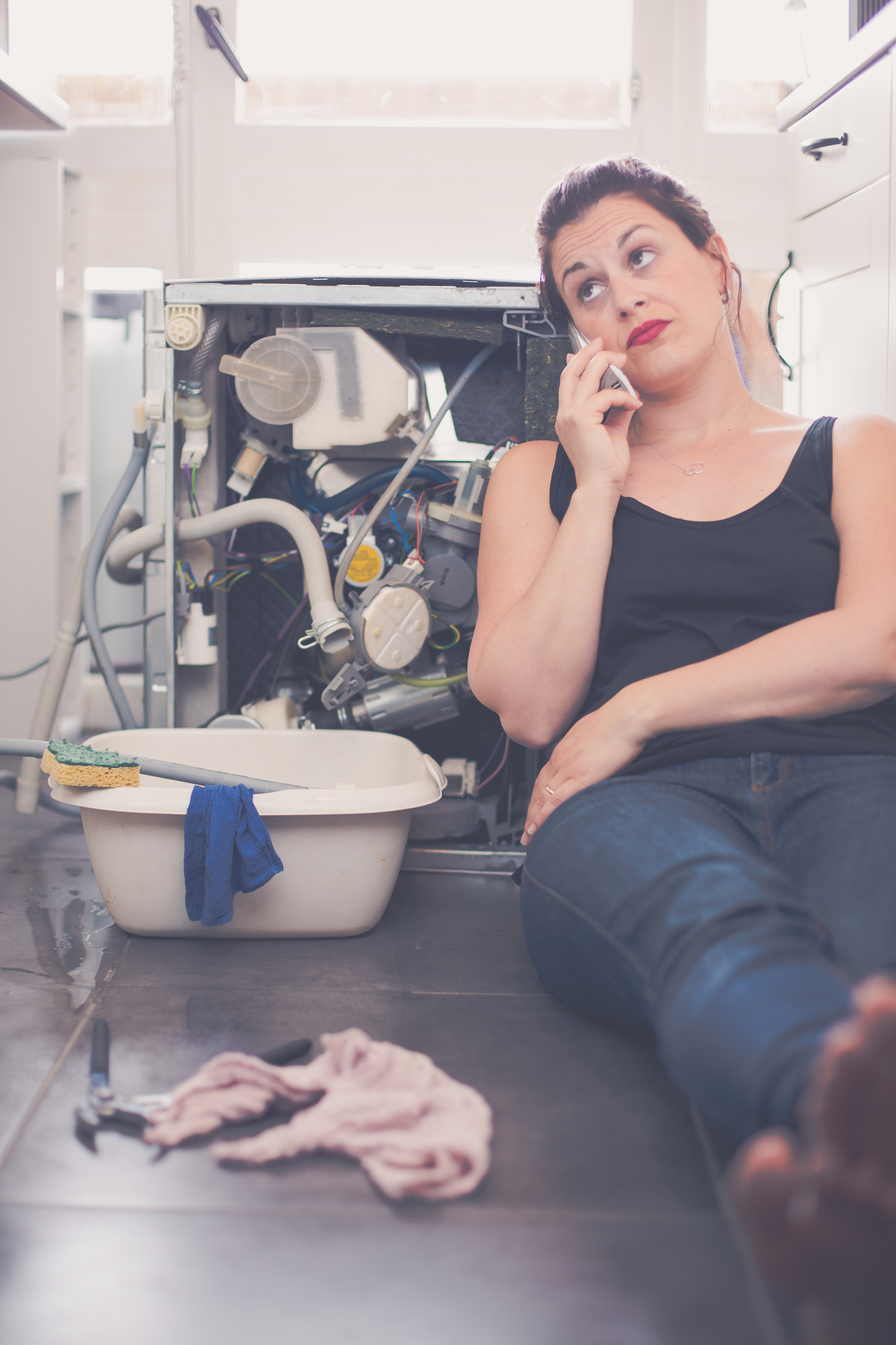 Woman is calling a plumber to repair the leak
